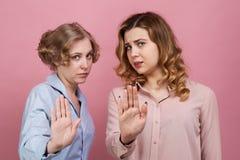 Dwa młodej dziewczyny w protestacyjnym dosięgają out przed one i żądają zatrzymywać i zatrzymywać Pojęcie nieporozumienie, odmowa zdjęcia stock