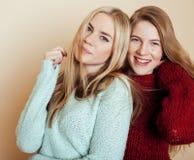 Dwa młodej dziewczyny w zima pulowerach indoors ma zabawę lifestyle Blond nastoletnich przyjaciół zamknięty up Fotografia Stock