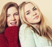 Dwa młodej dziewczyny w zima pulowerach indoors ma zabawę lifestyle Blond nastoletnich przyjaciół zamknięty up obraz royalty free