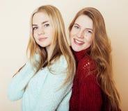 Dwa młodej dziewczyny w zima pulowerach indoors ma zabawę lifestyle Blond nastoletnich przyjaciół zamknięty up obrazy royalty free