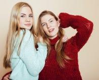 Dwa młodej dziewczyny w zima pulowerach indoors ma zabawę lifestyle Blond nastoletnich przyjaciół zamknięty up zdjęcie stock
