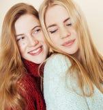 Dwa młodej dziewczyny w zima pulowerach indoors ma zabawę lifestyle Blond nastoletnich przyjaciół zamknięty up obraz stock