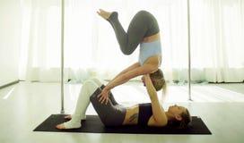 Dwa młodej kobiety ćwiczy akrobatyczny joga zdjęcie stock