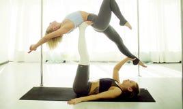 Dwa młodej kobiety ćwiczy akrobatyczny joga obraz royalty free