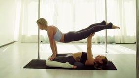 Dwa młodej kobiety ćwiczy akrobatyczny joga zdjęcie royalty free