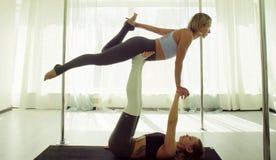 Dwa młodej kobiety ćwiczy akrobatyczny joga zdjęcia stock