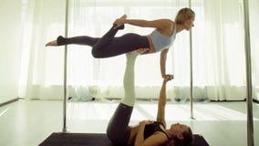 Dwa młodej kobiety ćwiczy akrobatyczny joga obraz stock