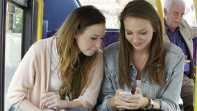Dwa młodej kobiety Czyta wiadomość tekstową Na autobusie zbiory