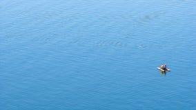 Dwa młodej kobiety na catamaran bierze sunbath po środku błękitnego jeziora przy słonecznym dniem Obraz Stock
