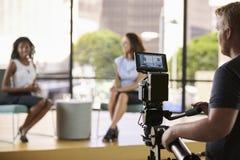 Dwa młodej kobiety na secie dla TV przeprowadzają wywiad, skupiają się na przedpolu, Zdjęcie Stock