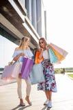 Dwa młodej kobiety niesie torby na zakupy przed centrum handlowym zdjęcia royalty free