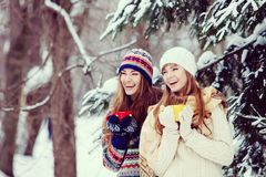 Dwa młodej kobiety pije herbaciany plenerowego i smil z kolorowymi filiżankami Obraz Stock