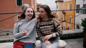 Dwa młodej kobiety siedzą na ławce i opowiadają Jeden one przedstawienie inny coś zbiory