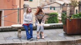 Dwa młodej kobiety siedzą na ławce Jeden one przedstawienie inny coś zdjęcie wideo