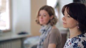 Dwa młodej kobiety siedzą, patrzeją, skiną, obracają jego głowę i one uśmiechają się, zdjęcie wideo