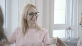 Dwa młodej kobiety siedzą w kawiarni i komunikują z ich przyjaciółmi zbiory wideo