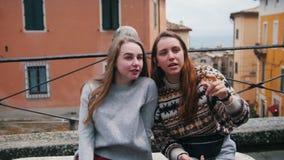 Dwa młodej kobiety siedzi i opowiada na ulicie Jeden one przedstawienie inny coś zbiory