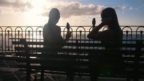 Dwa młodej kobiety siedzi na quay morze i je lody zbiory wideo