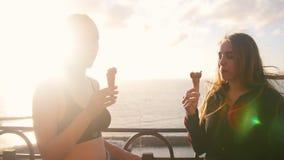 Dwa młodej kobiety stoi na dennym quay i je lody po trenować zbiory wideo