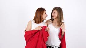 Dwa młodej kobiety uśmiecha się one i zakrywa jaźń z czerwoną koc zbiory