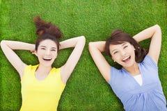 Dwa młodej kobiety uśmiechnięty lying on the beach na łące zdjęcia royalty free