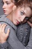 Dwa młodej kobiety w szarych pulowerach na popielatym tle piękny g Fotografia Stock