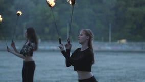 Dwa młodej kobiety wykonuje przedstawienie z płomień piłkami stoi na riverbank Sprawni fireshow artyści pokazuje mistrzostwo zbiory