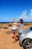 Dwa młodej kobiety z samochodowym spojrzeniem przy mapą obrazy royalty free