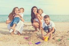 Dwa młodej matki i ich dzieci ma zabawę na plaży Zdjęcie Stock