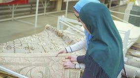 Dwa młodej muzułmańskiej kobiety wybierają dywanika w sklepie zamkniętym w górę zbiory