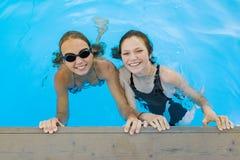 Dwa młodej nastoletniej dziewczyny ma zabawę w pływackim basenie zdjęcie stock