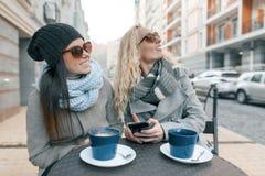 Dwa młodej one uśmiechają się modnej kobiety śmia się w plenerowej kawiarni, pijący kawę, opowiadający, tło miejskie zdjęcie stock