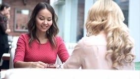 Dwa młodej pięknej dziewczyny siedzi w miastowej kawiarni z kawą i opowiadać Zdjęcie Royalty Free