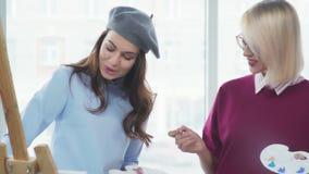 Dwa młodej pięknej kobiety w eleganckich ubraniach rysują w jaskrawym studiu, zdjęcie wideo