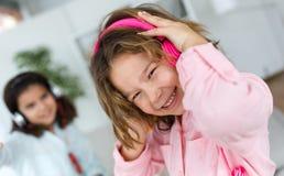 Dwa młodej siostry słucha muzyka i taniec w domu zdjęcie royalty free
