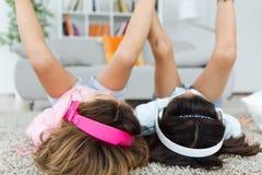 Dwa młodej siostry słucha muzyka i taniec w domu zdjęcie stock