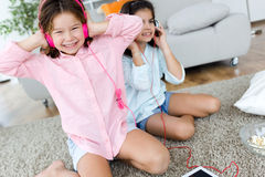 Dwa młodej siostry słucha muzyka i taniec w domu fotografia stock