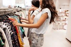 Dwa młodej uśmiechniętej szczupłej dziewczyny z długim ciemnym włosy, jest ubranym przypadkowego styl, zakupy w nowożytnym centru zdjęcie stock