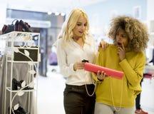 Dwa młodej wieloetnicznej kobiety kupuje kiesy w sklepie obrazy stock