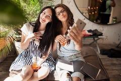 Dwa młodocianej uśmiechniętej pięknej szczupłej dziewczyny z długim ciemnym włosy, jest ubranym przypadkowych ubrania, siedzą obo obrazy stock
