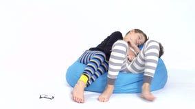 Dwa młodszego brata śpią na bobowej torbie przy białym tłem zdjęcie wideo
