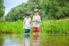 Dwa młodszego brata bawić się z papierowymi łodziami rzeką na ciepłym i pogodnym letnim dniu Obraz Stock