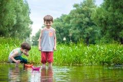 Dwa młodszego brata bawić się z papierowymi łodziami rzeką na ciepłym i pogodnym letnim dniu Zdjęcia Royalty Free