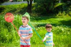 Dwa młodszego brata bawić się z papierowymi łodziami rzeką na ciepłym i pogodnym letnim dniu Obrazy Stock