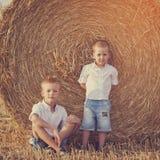 Dwa młodszego brata siedzi blisko haystack wewnątrz Zdjęcia Royalty Free