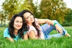 Dwa młodych dziewczyn szczęśliwy kłamstwo na trawie Zdjęcie Royalty Free