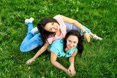 Dwa młodych dziewczyn szczęśliwy kłamstwo na trawie Obrazy Stock