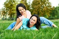 Dwa młodych dziewczyn szczęśliwy kłamstwo na trawie Fotografia Royalty Free