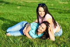 Dwa młodych dziewczyn szczęśliwy kłamstwo na trawie Obraz Royalty Free