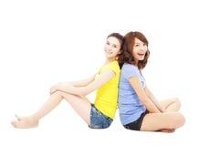Dwa młodych kobiet obsiadanie i z powrotem popierać Zdjęcia Royalty Free